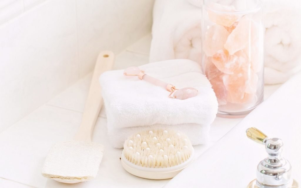 An image you could include in your self care box. On a counter lie a dry brush, a rose quartz roller, a soft towel and a jar with pieces of rose quartz.