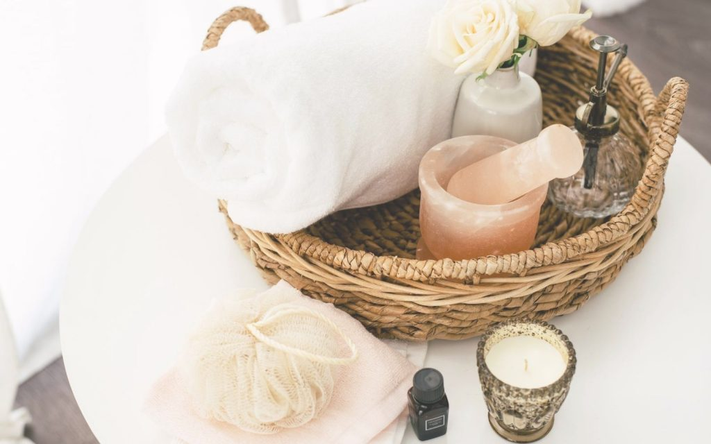 Self care ideas for fall: a self care kit with candles, morter and pestle and soft white towels